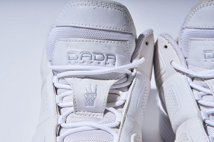 タンのシューレースガードには、DADAの象徴である王冠とバスケットボールのゴールネットを組み合わせたロゴを配置