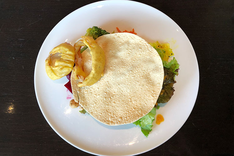 前菜の上のパパドは粉々に砕いて、サラダにまぶすのが基本