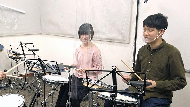 「田中さんは左手に力が入っていますね。リラックスして」と今村先生からアドバイスを受け、「無意識のうちにそうなっているんですね」と納得する田中部員