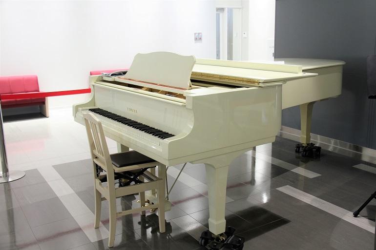 待合エリアの白いピアノ。時には、コンサートも開かれるそうだ