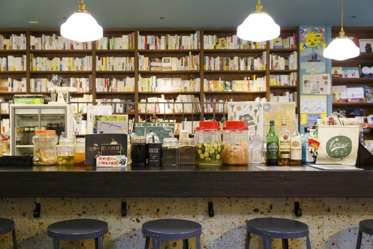カフェ「出町座のソコ」のカウンター。書棚にぎっしりと並ぶ本は「CAVA BOOKS」の選書