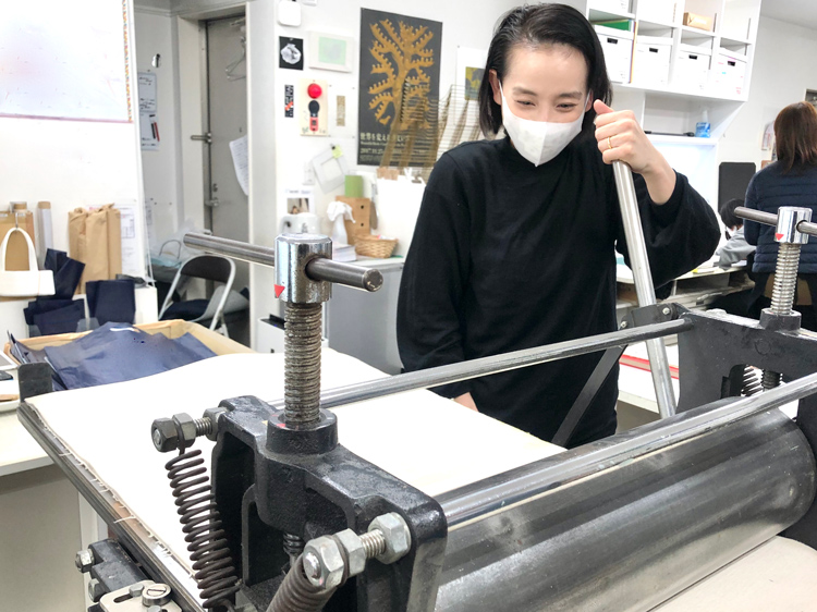 ゆっくりとプレス機を回し、和紙に版画を転写する作業