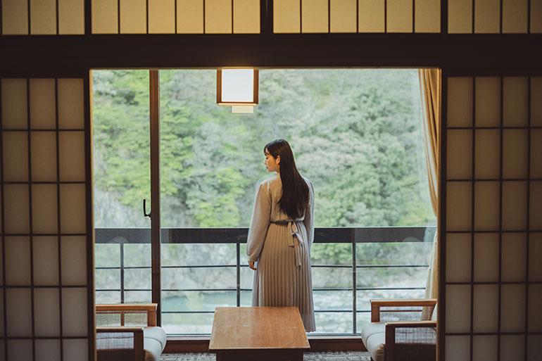 窓の景色が新緑に覆われ美しい。そこに女性を立たせることで情緒を醸し出す。旅館の室内は被写体に複数の色温度が違う光があたる「ミックス光」になりやすいので、ホワイトバランスを変えながら撮るのがコツ