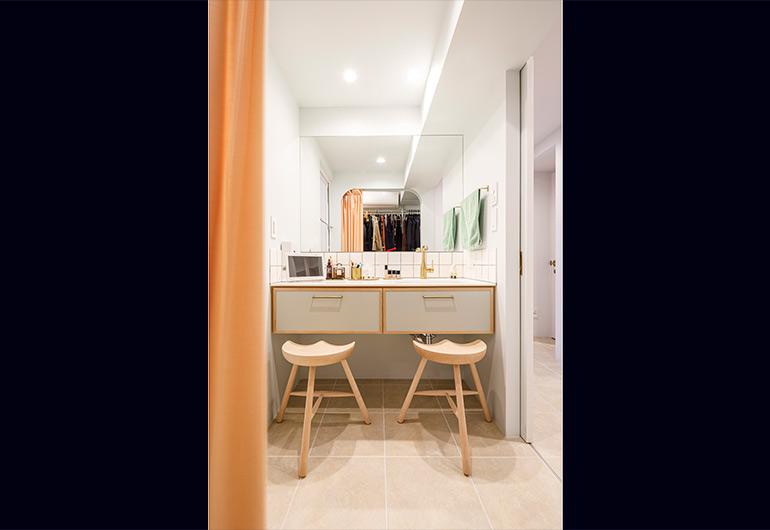 2人が横に並んで座れる洗面室。鏡に映ったアーチ開口の奥がウォークインクローゼット