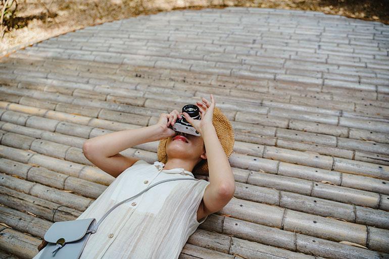 竹林の小径を歩く。途中、竹でできた円形のベンチがあり、そこに寝転んで空を見上げると、竹がカーブを描いてしなっている光景が目に入る。観光客で賑(にぎ)わうシーズンに行くと、その休憩場所で皆が寝ながら竹林を見上げていて面白い。一緒に旅したモデルさんが寝転んで写真を撮影している瞬間をパチリ