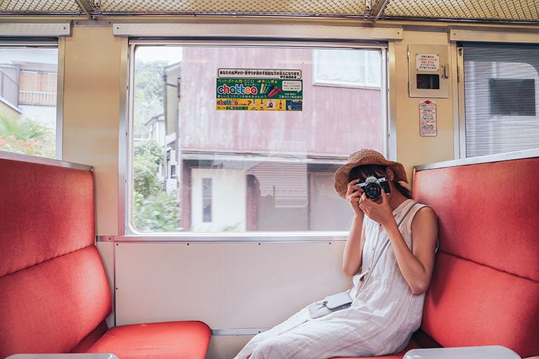 私が好きな赤いシートの電車。写真には色というものが重要で、赤いシートはそれだけで絵になるのだ。そこにモデルさんに腰掛けてもらい、こちらにカメラを向けてもらう。それだけで旅の楽しさを演出できるし、カメラを手に持つ彼女も素敵に写る