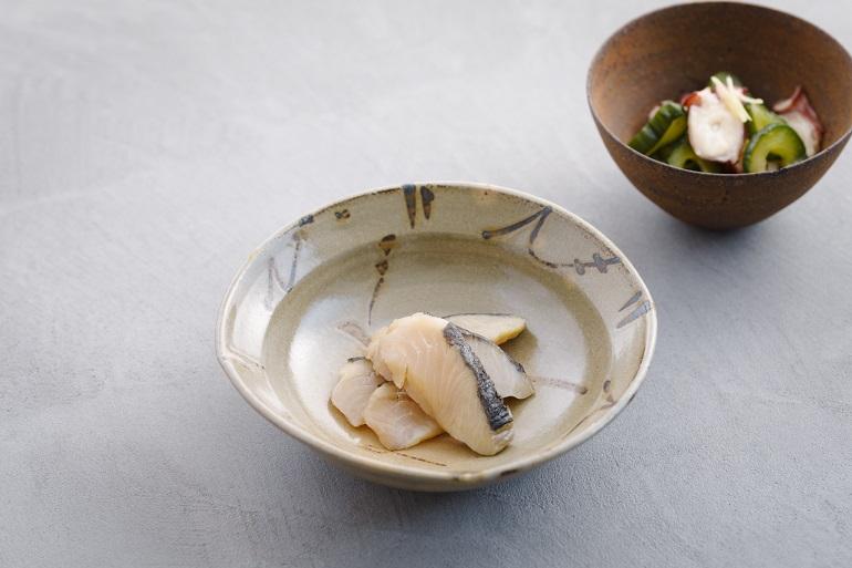 酢〆した鰆(サワラ)をもち米の藁(わら)で蒸した「〆鰆燻製(くんせい)」(左・1,512円)は杯が進む一品。肉厚のタコの食感と滋味深い塩ポン酢があと引く味わい「下津井タコ」(右・1,296円)。上記含む5品セットでお値打ちな「晩酌セット」(6,480円)も