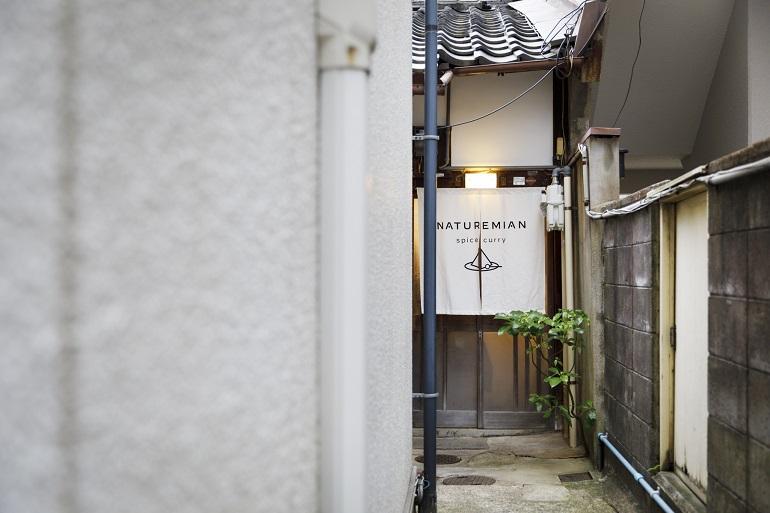 家と家の外壁に挟まれた、細い路地の奥。間口の狭さが特徴的な京町家の造り