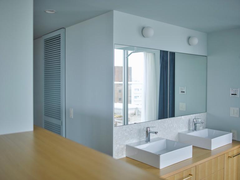 ダブルシンクのゆったりとした洗面カウンター。壁面には貝殻でできたシェルタイルを