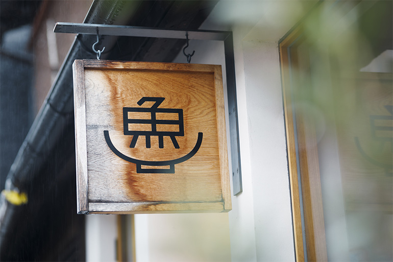 漢字とめし碗(わん)のフォルムを生かしたロゴ。ひと目で魚が看板メニューとわかる