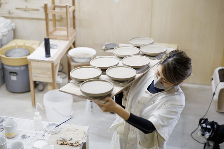 制作途中のうつわを運ぶ。成形したうつわは乾燥、素焼きを経て、釉薬を掛け本焼きへ。完成まで2カ月ほどかかる