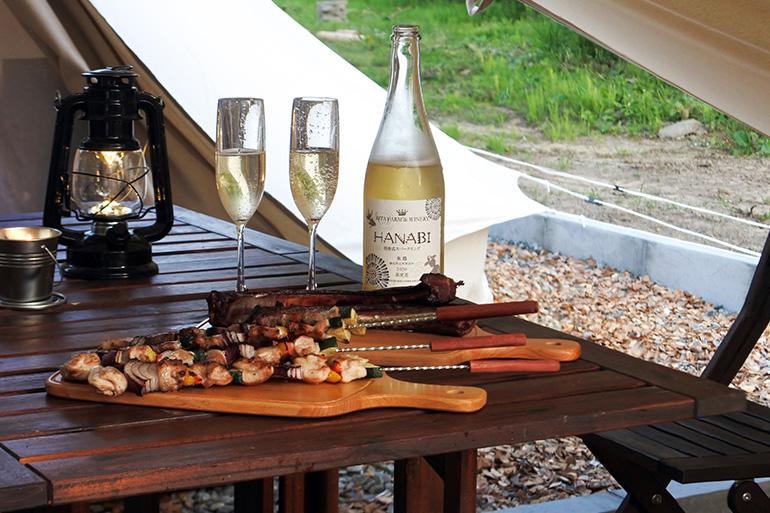 北島豚や桜姫鶏、EBIJIN鹿など、道産の食材を盛り合わせた「道産ブランドBBQ」と、リタ・ファーム&ワイナリーの「田舎式スパークリングワイン HANABI」を一緒に