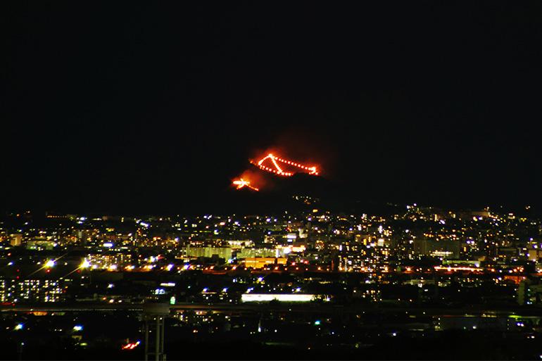 それぞれ8時10分、同15分に点火される「船形万燈籠(とうろう)送り火」「左大文字送り火」。左大文字には松明行列を作って点火に向かうという風習がある=Getty Images(2018年8月16日)