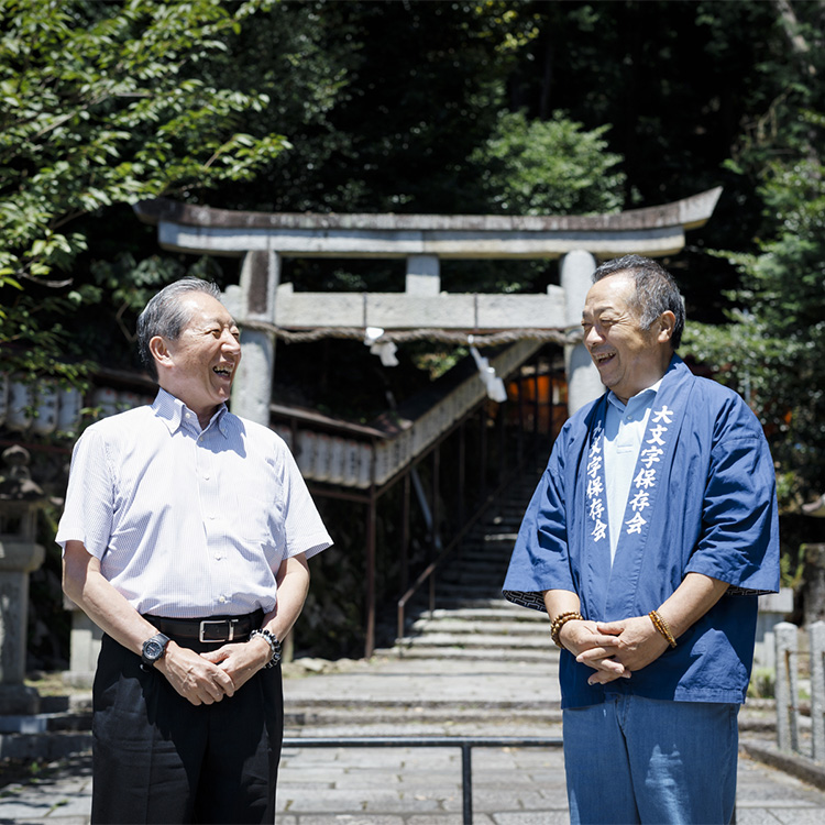 佛教大学歴史学部の八木透教授(左)と大文字保存会の長谷川英文会長。保存会の集会所隣の神社で