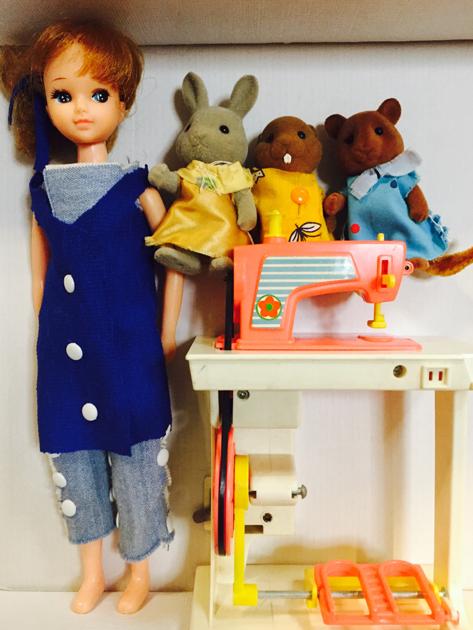 手作り衣装を着せたお人形たちとおもちゃのミシン