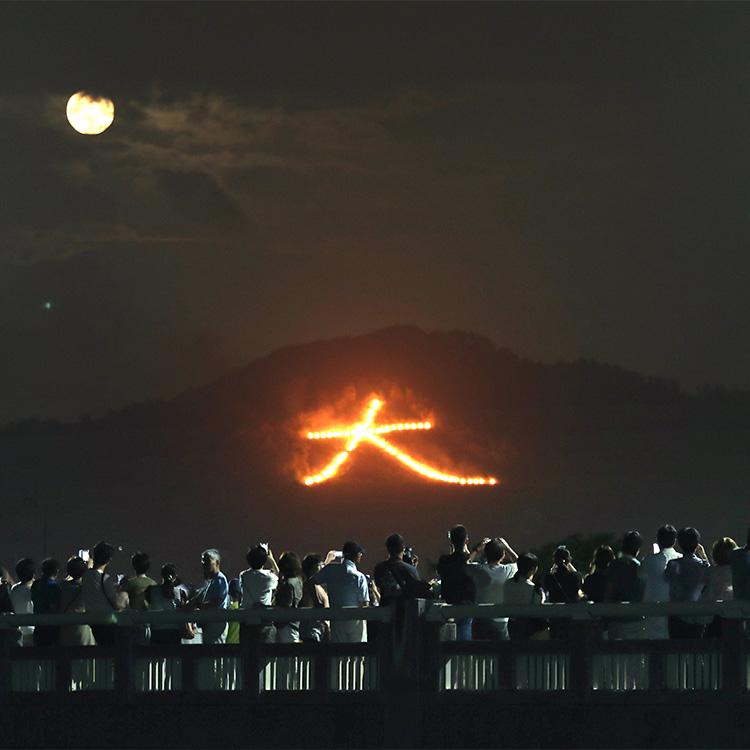 東山・如意ヶ嶽(にょいがたけ)の斜面に浮かび上がった「大」の文字。雲の合間から月も姿を現した=2019年8月16日©朝日新聞社