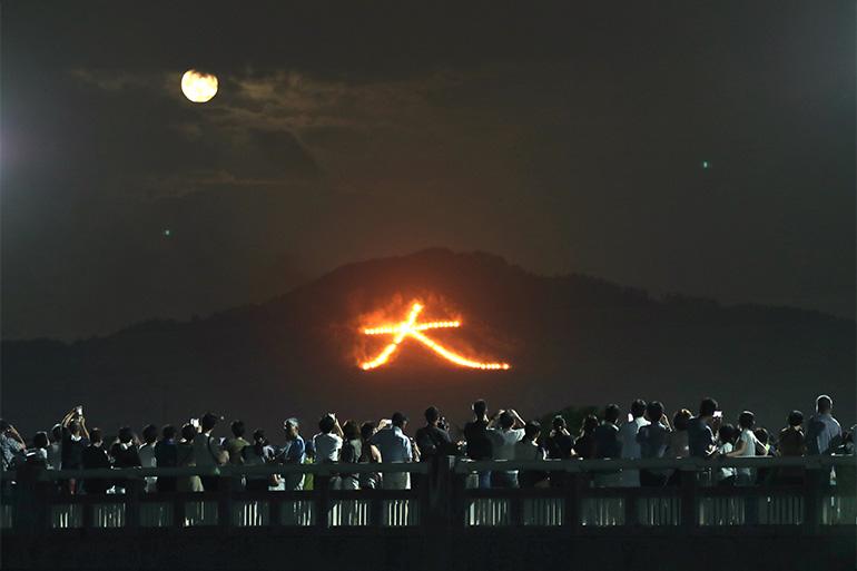 東山・如意ヶ嶽の斜面に浮かび上がった「大」の文字。雲の合間から月も姿を現した=2019年8月16日©朝日新聞社