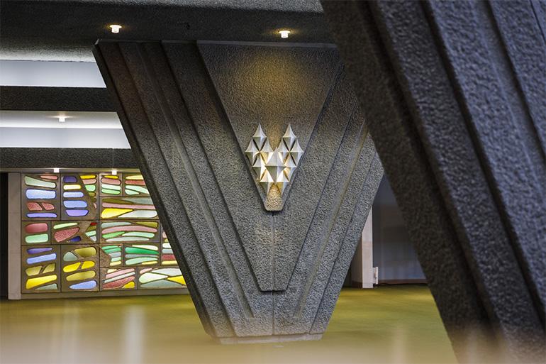 V字の柱には折り紙から着想した照明が。奥のステンドグラスは、若手の美術家を集めた「A・A・A(Association des Artistes pour l'Architecture)」が制作した