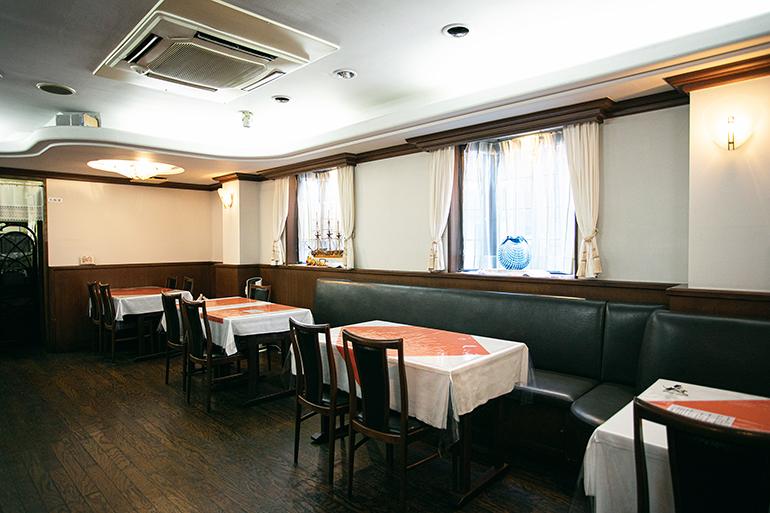 余裕をもってテーブルが配置された1階のダイニング。2階には個室があり、3階でオーナー夫妻が暮らす一軒家レストラン