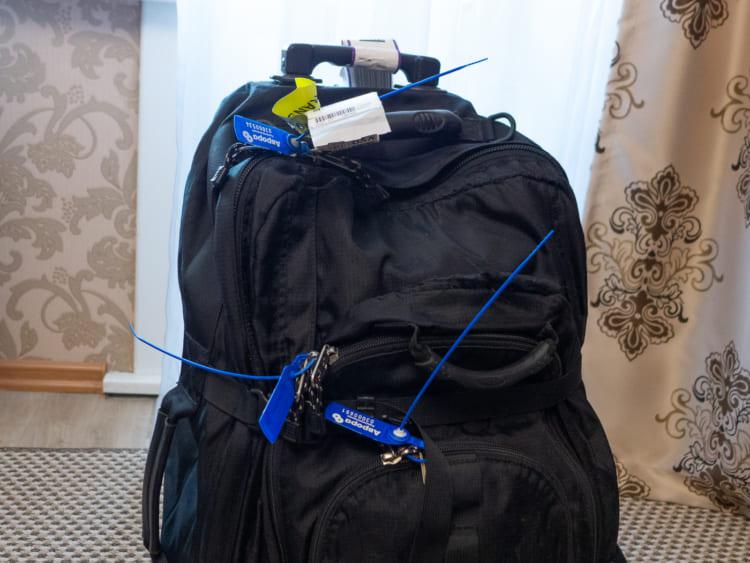 荷物の開け口は、強いプラスチックひもで閉じられていた