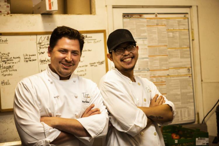 エグゼクティブシェフのミカさん(左)とリードコックのキンさん。ホワイトボードにアイデアを書き出しレストランとバーカウンターメニューを二人で決めている