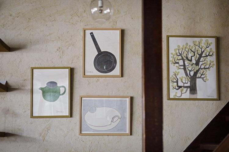壁にはダイモンさんの作品が飾られている。モチーフは暮らしの道具や植物、旅の風景などが多い。購入も可能