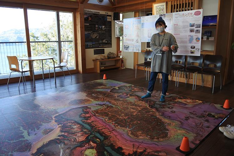 黄金崎にある「こがねすと」の床には、急峻(きゅうしゅん)具合を赤から白のグラデーションで示す赤色立体地図が。険しい地形の伊豆半島南西部が、かつての海底火山群を示しています