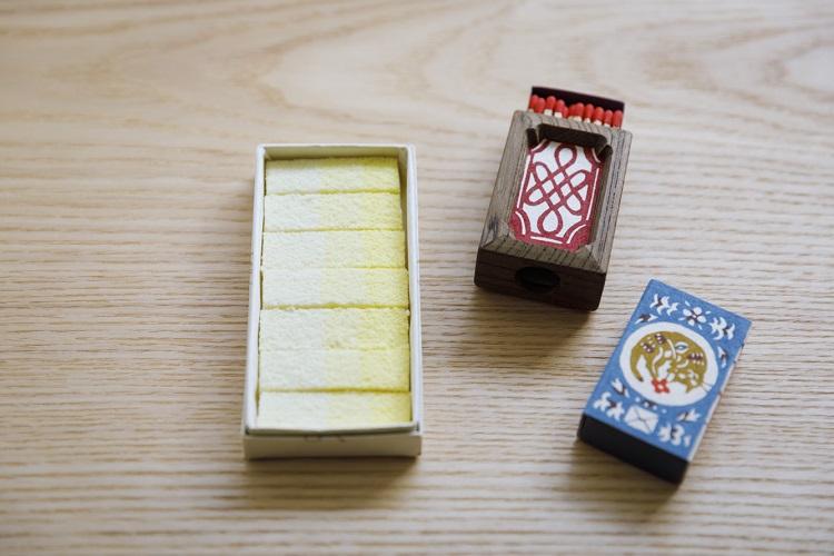 型絵染作家・関美穂子氏が紙箱の図案を、木工作家・佃眞吾氏が木枠の箱を手がけた「マッチ箱」(右側二つ、1箱15,000円)。季節によって色や模様が変わる落雁(らくがん)「うつろひ」(900円、いずれも税込み)