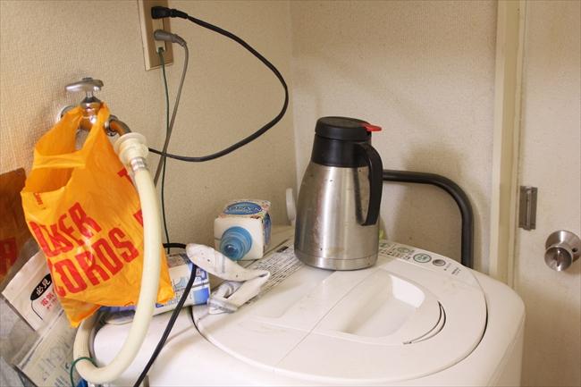 洗濯機の上に、片方の靴下とポット