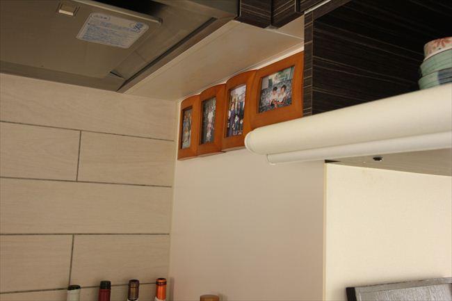 ガス台の上に四つの額。「台所は私の仕事場。だから自分の両親の写真を飾っています」