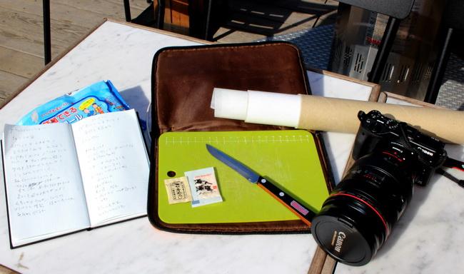 取材の七つ道具。ノート、カメラはもちろん、ミニまな板やナイフ、台紙にするクッキングペーパーも必携