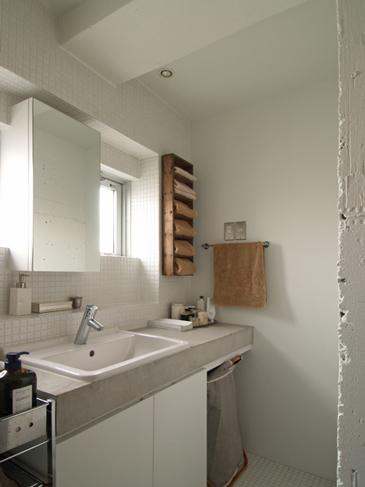 モルタルと白いタイルでつくった洗面所。木の棚はアンティーク