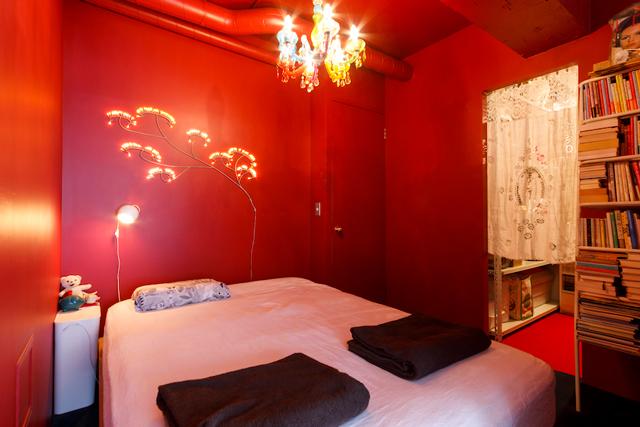 寝室は赤い壁に緑のカーペットで、映画「アメリ」風に。照明はTsé &Tsé associées(ツェツェ・アソシエ)のもの