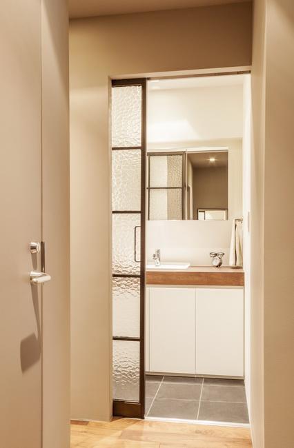 サニタリーと廊下を仕切る、型板ガラスのアイアンサッシ。洗面所も白を基調として明るくスッキリと