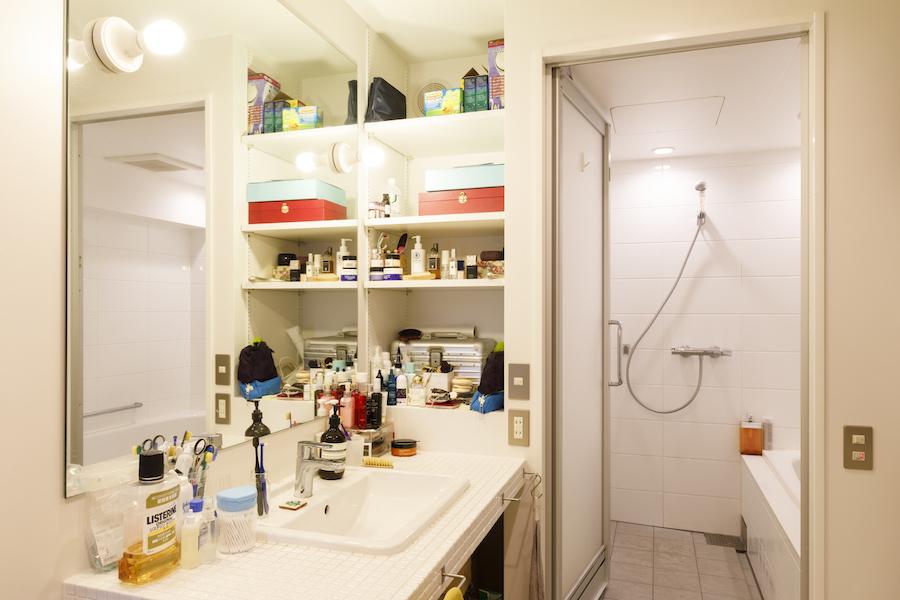 白いタイルを用いた洗面。奥はバスルーム