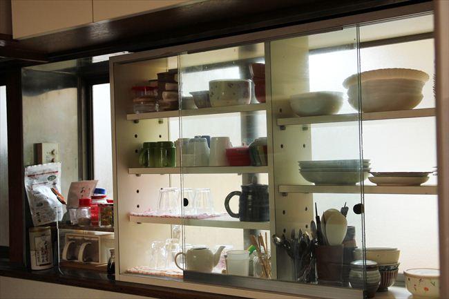 白い棚は夫が窓のサイズに合わせて作った。家族のふだん使いを収納