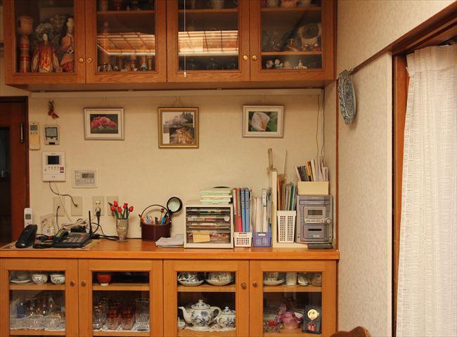 吊り戸棚には人形など。下段の食器棚は来客用グラスなど。棚は夫の作