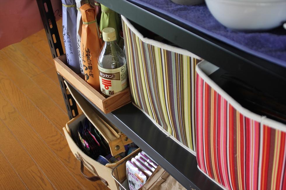 本棚につかっていたシェルフを台所用品の収納に。ストライプの布ボックスにはビニール袋と紙袋を