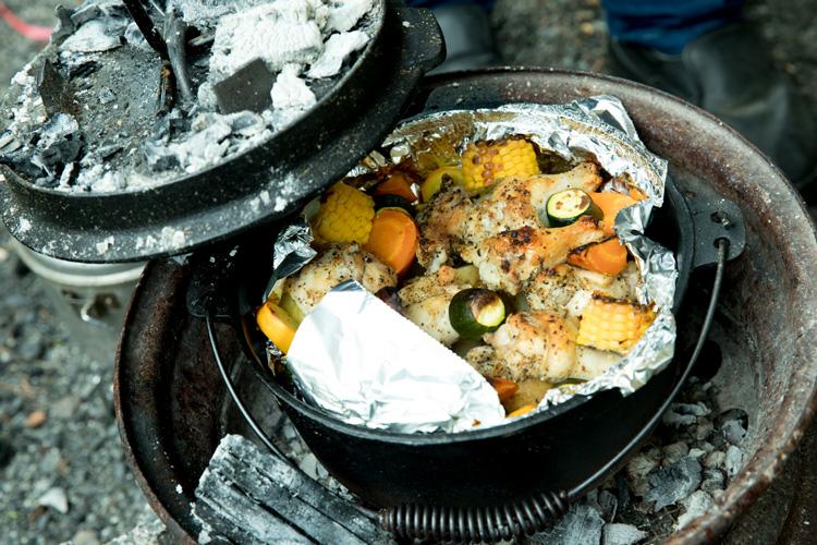 ダッチオーブンにハーブ塩で下味をつけた手羽元と野菜を入れて約45分強火にかけるだけで出来上がり!蓋の上にも炭を乗せて上下から熱を通すと効率がいい