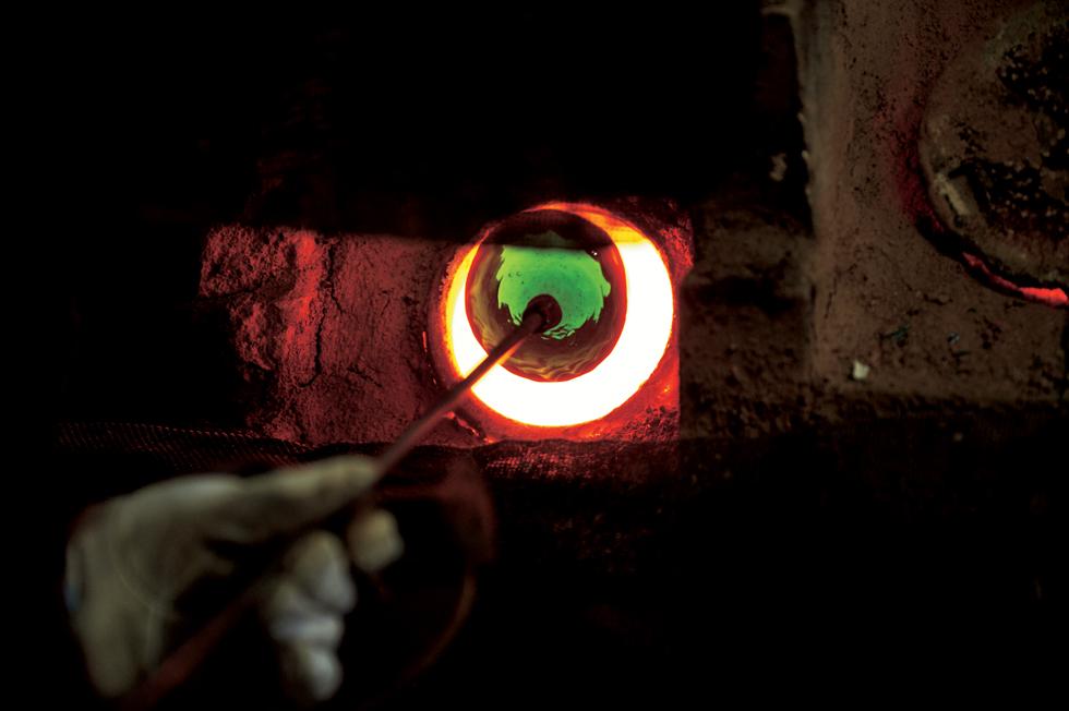 熱と時間との闘い。1300度に達し赤々と燃える坩堝(るつぼ)に、ガラス生地を投入する