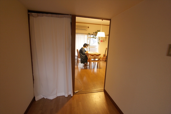 台所からダイニングをのぞむ。左のカーテンはプライベートな部屋。右は仕事場でもある