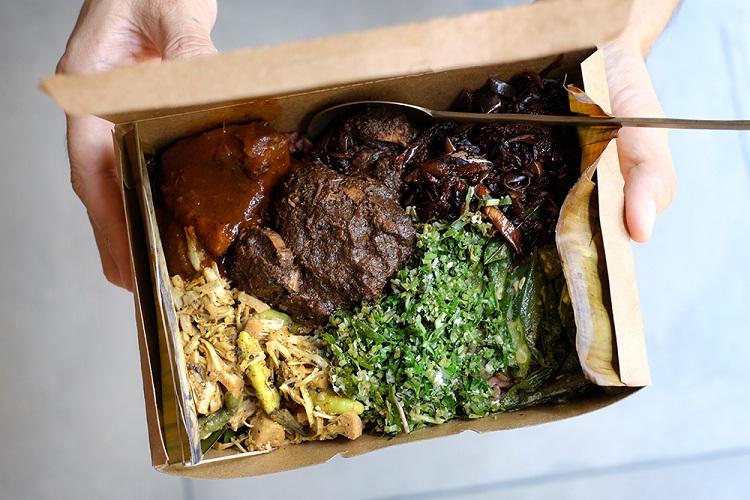 真ん中にあるのが人気メニューのひとつ、アンブルティヤル(マグロの胡椒カレー)。スリランカの良質な胡椒をたっぷりと使い、そのうまみが堪能できる。これはテイクアウト用ボックスに入れられたライス&カリー
