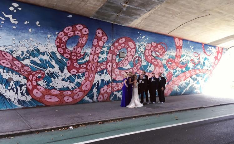 駅の出口付近の壁画前で記念写真を撮影する結婚式中のカップル