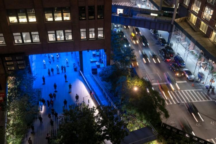 ハイラインはホテルや商業施設などの下も通過している。上空からハイラインを撮影した写真。ビルの下は青く光っていた Photography by Timothy Schenck