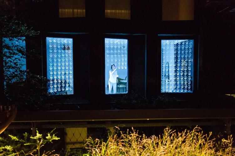 ビルの窓ガラスの前で清掃作業者のような動きをするパフォーマーに下から光を当てるウィンドウパフォーマンス。パフォーマーによって違うアプローチをとる Photography by Liz Ligon