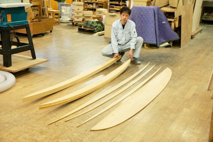 角田さんが持っているのが、サーフボードのサイド部分に使う「レール」と呼ばれるパーツ。向かって右側はサーフボード内の「リブ」と呼ばれる骨組みの曲線を作る器具「ジグ」