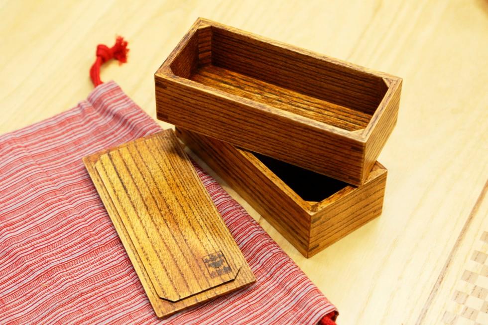 会津塗の漆で仕上げた会津桐弁当箱「会津三味」は会津木綿の袋とセット(税込14,040円)