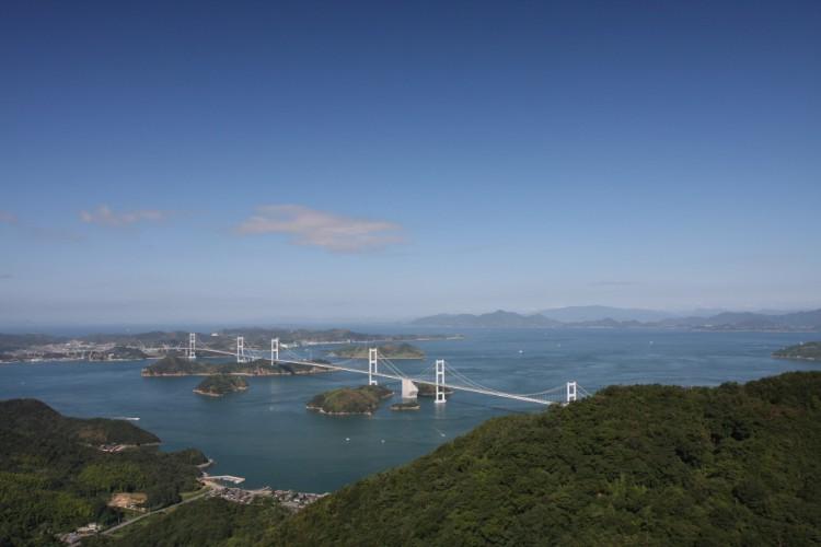 標高307.8mの亀老山展望公園のパノラマ展望台ブリッジから見える「来島海峡大橋」。世界初の三連吊橋で中央の橋がしまなみ海道にあたり、サイクリングコースとしても高い人気を誇る