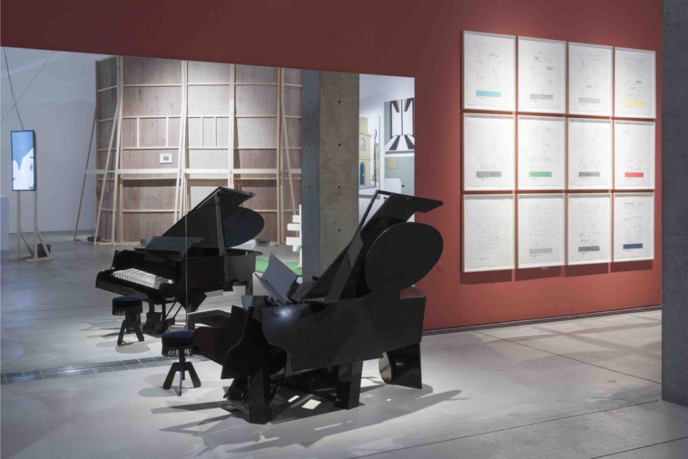 会場風景(ギャラリー2)(撮影:鈴木 薫) 福田繁雄さんの立体作品「アンダーグランドピアノ」。実物は断片が複雑に組み合わされた物体だが、鏡に映る姿はグランドピアノに見える