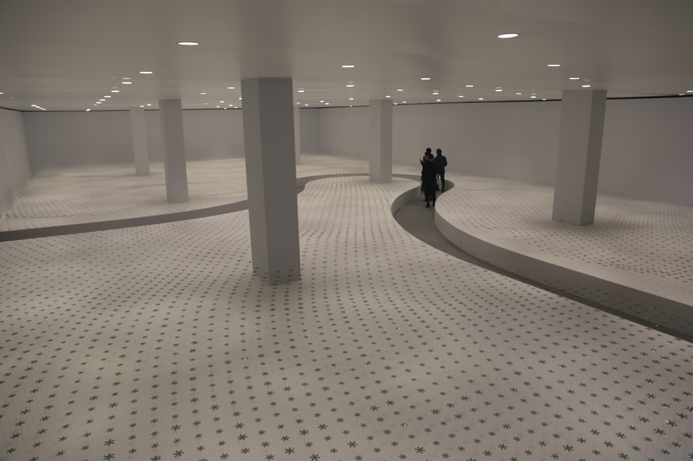 nendoは「Breeze of Light」をテーマに、約32メートル×約18メートルの空間に115灯の照明と約17000本の花型の偏光板を置き、「光と影の動きで心地よい風を感じさせる」(代表の佐藤オオキ氏)インスタレーションを展開